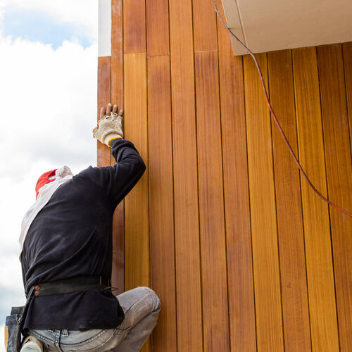 Worker installing siding with a wood grain appearance.